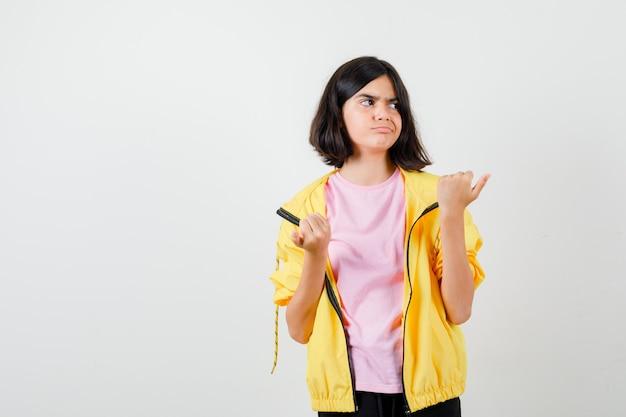 Porträt eines jugendlichen mädchens, das mit dem daumen nach rechts zeigt, während es die erhobene hand in t-shirt, jacke zeigt und verärgerte vorderansicht schaut