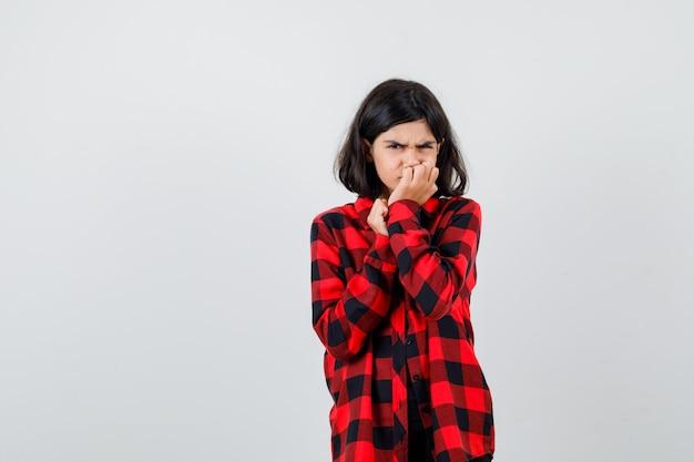 Porträt eines jugendlichen mädchens, das sich in einem lässigen hemd die nägel beißt und deprimierte vorderansicht schaut