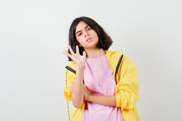 Porträt eines jugendlichen mädchens, das stoppgeste in t-shirt, jacke und gereizter vorderansicht zeigt