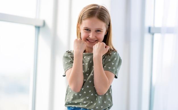 Porträt eines jugendlichen schönen mädchenmodells, das sich als boxer in einem hellen raum ausgibt und eine weibliche kinderschule lächelt...