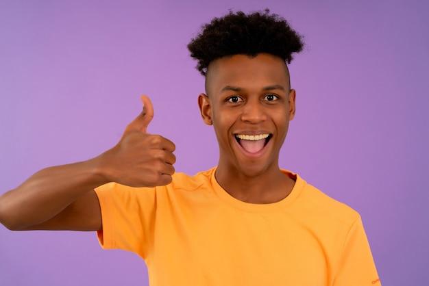 Porträt eines jungen afro-mannes, der die kamera betrachtet und lächelt, während er sich daumen zeigt.