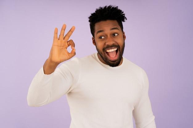 Porträt eines jungen afro-mannes, der mit den händen eine gute geste macht und lächelt, während er vor isoliertem hintergrund steht.