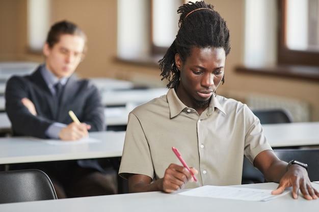 Porträt eines jungen afroamerikanischen mannes, der in der schule eine prüfung ablegt, während er am schreibtisch im college sitzt und nachdenkt, platz kopieren