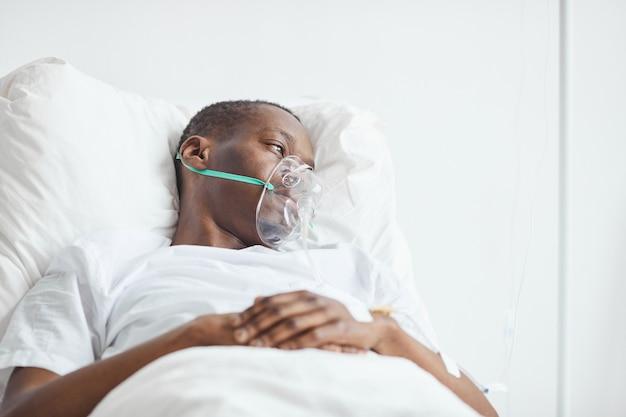Porträt eines jungen afroamerikanischen mannes im krankenhausbett mit sauerstoffmaske, kopierraum