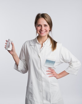 Porträt eines jungen apothekers, der pillen zeigt