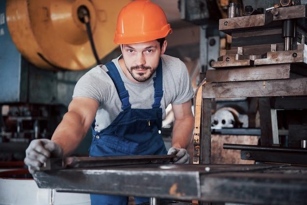 Porträt eines jungen arbeiters in einem schutzhelm in einer großen abfallrecyclingfabrik.