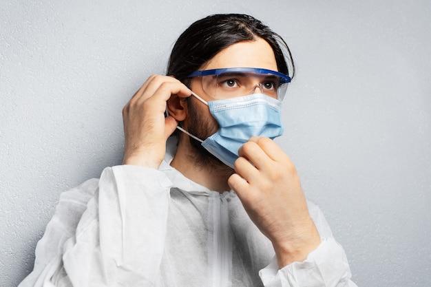 Porträt eines jungen arztmannes, der psa-anzug trägt und medizinische gesichtsmaske gegen coronavirus und covid-19 aufsetzt.