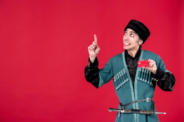 Porträt eines jungen aserbaidschanischen mannes in traditioneller tracht mit kreditkarte auf rot