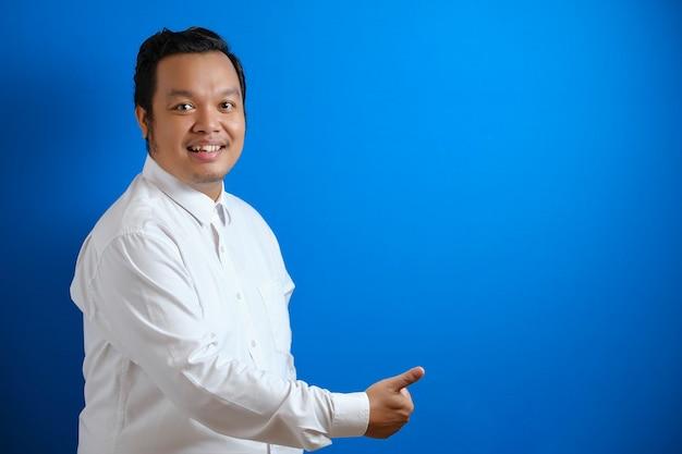 Porträt eines jungen asiatischen geschäftsmannes mit weißem hemd, der in die kamera schaut, lächelt und zeigt asiatische grußgeste einzeln auf blauem hintergrund