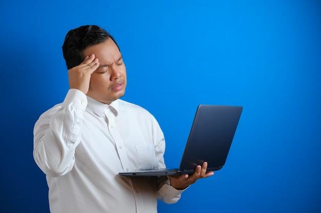 Porträt eines jungen asiatischen geschäftsmannes sah müde aus und litt unter steifen kopfschmerzen, nachdem er zu lange am laptop gearbeitet hatte