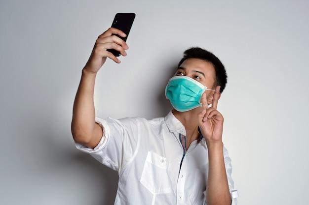 Porträt eines jungen asiatischen mannes, der eine gesundheitsmaske trägt und ein selfie mit seinem telefon mit victory-handpose macht