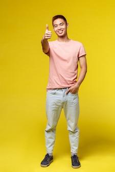 Porträt eines jungen asiatischen mannes, der geste über gelber wand zeigt
