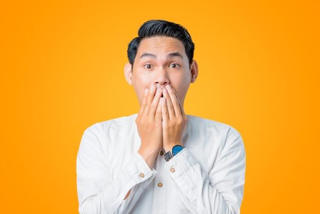 Porträt eines jungen asiatischen mannes, der mit einer hand schockiert ist, die den mund bedeckt