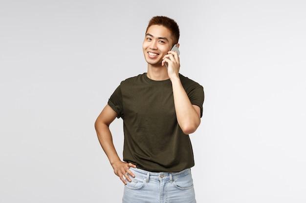 Porträt eines jungen asiatischen mannes, der per telefon spricht