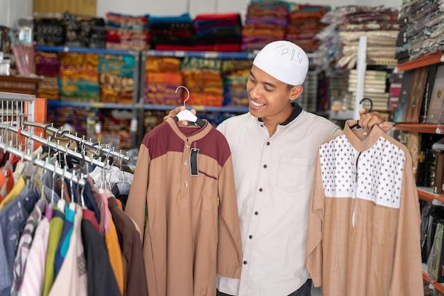 Porträt eines jungen asiatischen muslimischen mannes, der kleidung im laden einkauft
