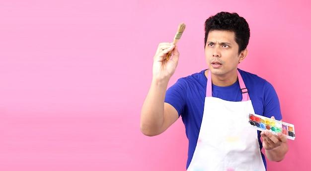 Porträt eines jungen asien-mannmalers mit der palette, die auf rosa hintergrund im studio steht