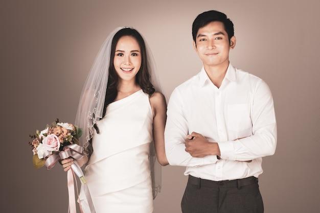 Porträt eines jungen attraktiven asiatischen paares, das händchen hält, mann trägt weißes hemd, frau trägt