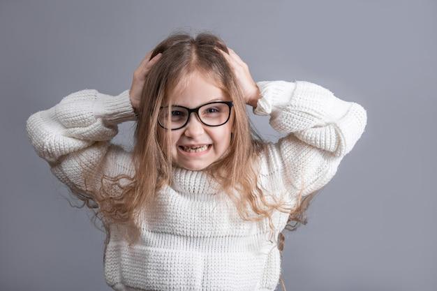 Porträt eines jungen attraktiven kleinen mädchens mit händen auf dem kopf in einem weißen pullover genervt gereizt gereizt, ihr haar für nervöse meinungsverschiedenheiten herausziehend