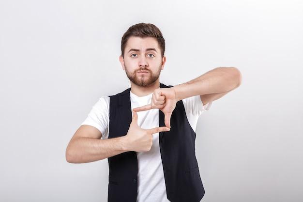 Porträt eines jungen attraktiven mannes mit dunklem haar im weißen hemd auf grauem hintergrund. männerhände machen rahmen