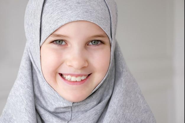 Porträt eines jungen attraktiven muslimischen 9-jährigen mädchens mit grauem hijab und traditioneller kleidung, das in die kamera schaut und auf hellem hintergrund lächelt. nahaufnahme