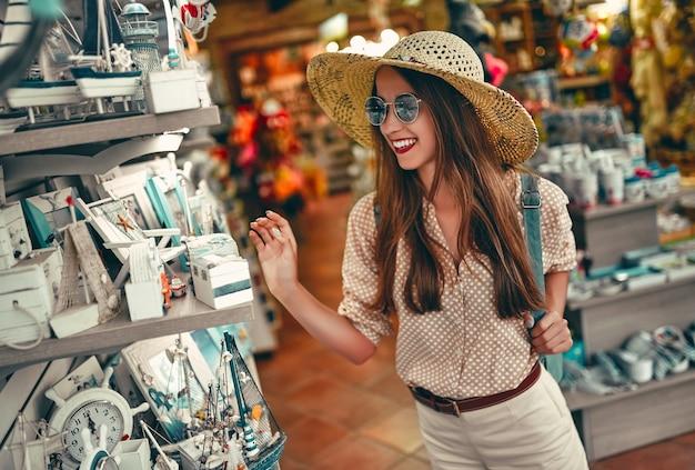 Porträt eines jungen attraktiven touristenmädchens in einem strohhut, einer bluse und einer sonnenbrille, die um den stadtmarkt herumgehen und dekorative innenausstattung auswählen. das konzept des tourismus, reisen.