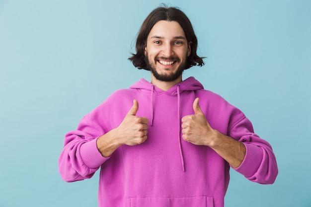 Porträt eines jungen bärtigen brünetten mannes mit hoodie, der isoliert über blauer wand steht und daumen nach oben zeigt