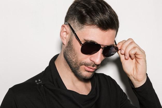 Porträt eines jungen bärtigen gutaussehenden mannes mit sonnenbrille, der vor der kamera posiert, isoliert über weißer wand