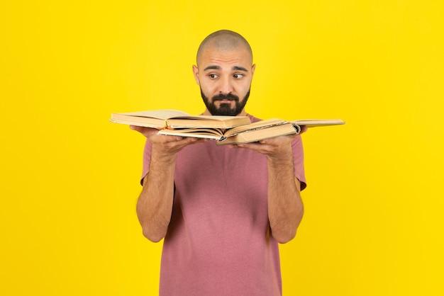 Porträt eines jungen bärtigen mannes, der geöffnete bücher über gelber wand hält.