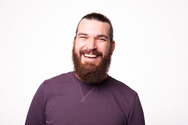 Porträt eines jungen bärtigen mannes, der in die kamera lächelt