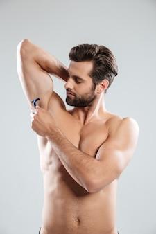 Porträt eines jungen bärtigen mannes, der seine achselhöhle rasiert