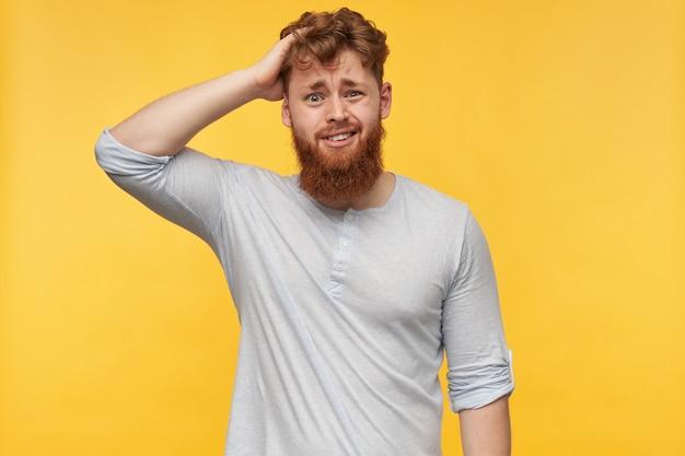Porträt eines jungen bärtigen mannes mit roten haaren, trägt ein leeres t-shirt und berührt seinen kopf auf gelb