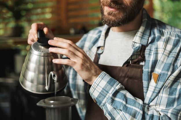 Porträt eines jungen barista-mannes mit schürze, der kaffee macht, während er im straßencafé oder kaffeehaus im freien arbeitet?