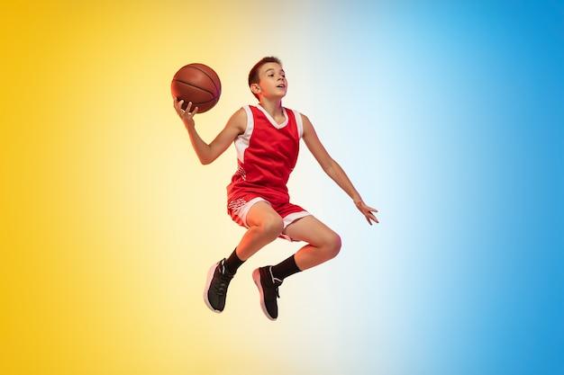 Porträt eines jungen basketballspielers in voller länge mit ball auf gradientenhintergrund