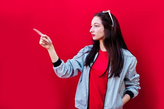 Porträt eines jungen brünetten mädchens, das auf flachem rotem hintergrund nach rechts zeigt