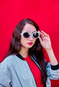 Porträt eines jungen brünetten mädchens, das ihre sonnenbrille auf flachem rotem hintergrund abnimmt