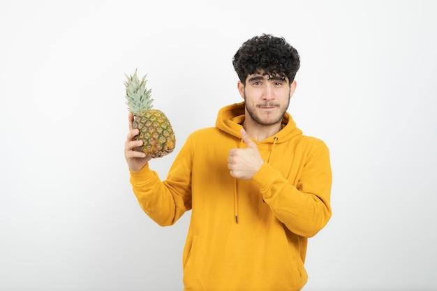 Porträt eines jungen brünetten mannes, der daumen oben zeigt und ananas hält.