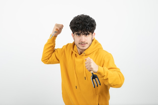 Porträt eines jungen brünetten mannes, der gartenwerkzeug steht und hält.