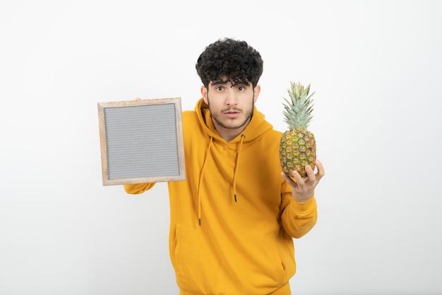 Porträt eines jungen brünetten mannes, der grauen rahmen mit ananas steht und hält. Premium Fotos