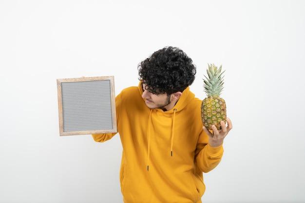 Porträt eines jungen brünetten mannes, der grauen rahmen mit ananas steht und hält.