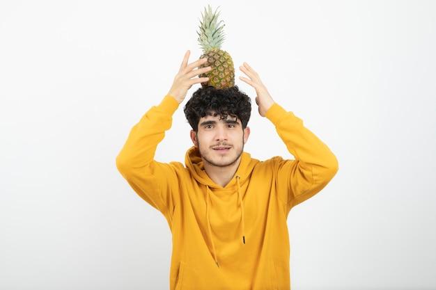 Porträt eines jungen brünetten mannes, der steht und ananas über kopf hält.