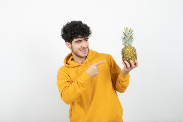 Porträt eines jungen brünetten mannes, der steht und auf ananas zeigt.