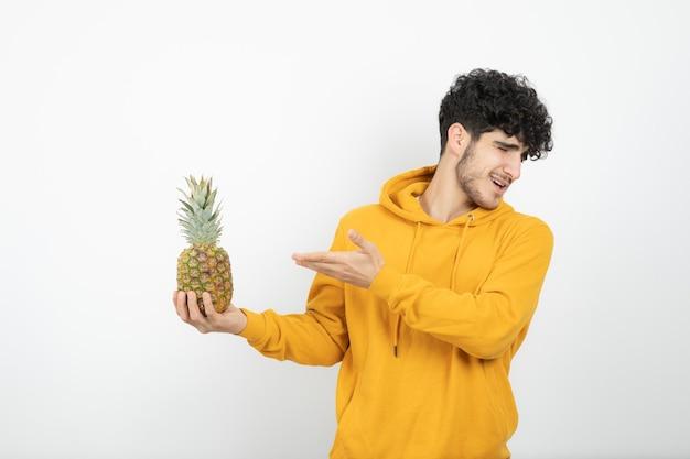 Porträt eines jungen brünetten mannes stehend und ananas haltend.
