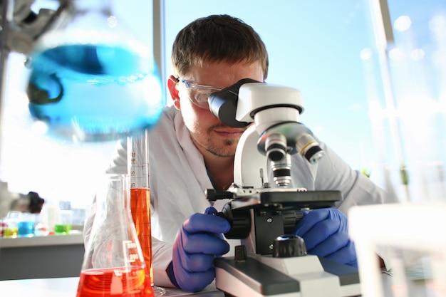 Porträt eines jungen chemikers, der im binokularen schaut