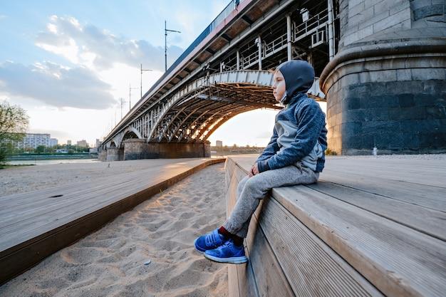 Porträt eines jungen, der am strand nahe der brücke sitzt