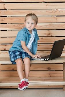 Porträt eines jungen, der auf bank unter verwendung des laptops sitzt