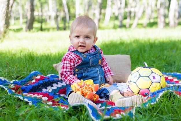 Porträt eines jungen, der auf einer decke auf einem frischen gras in einem stadtpark im sommer sitzt