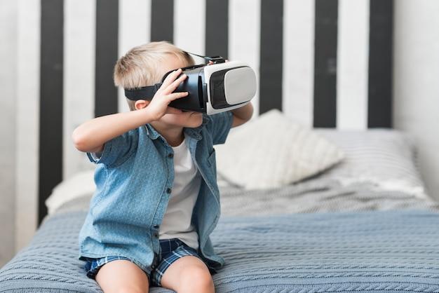 Porträt eines jungen, der auf tragenden schutzbrillen der virtuellen realität des betts sitzt