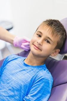 Porträt eines jungen, der auf zahnmedizinischem stuhl sich lehnt