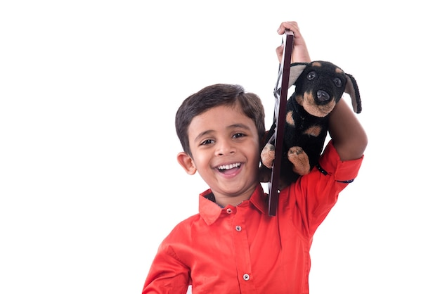 Porträt eines jungen, der ausgestopftes spielzeughaustier mit rahmen auf einem weiß hält