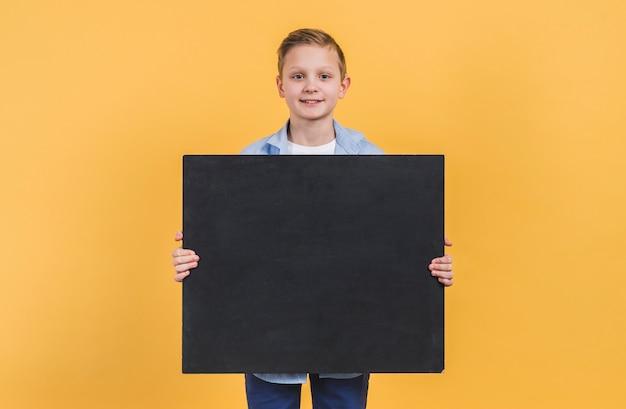 Porträt eines jungen, der die schwarze tafel steht gegen gelben hintergrund hält
